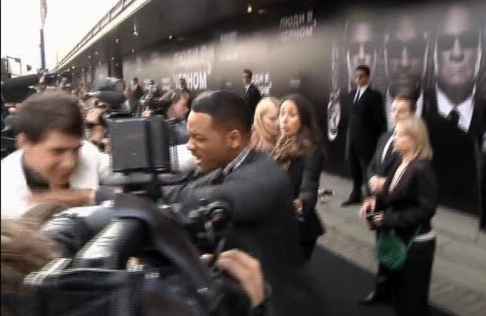 Photo -   In this video image taken from AP video U.S. actor Will Smith, center, pushes reporter Vitalii Sediuk, white suit, from the Ukrainian television channel 1+1 on the red carpet before the premiere of