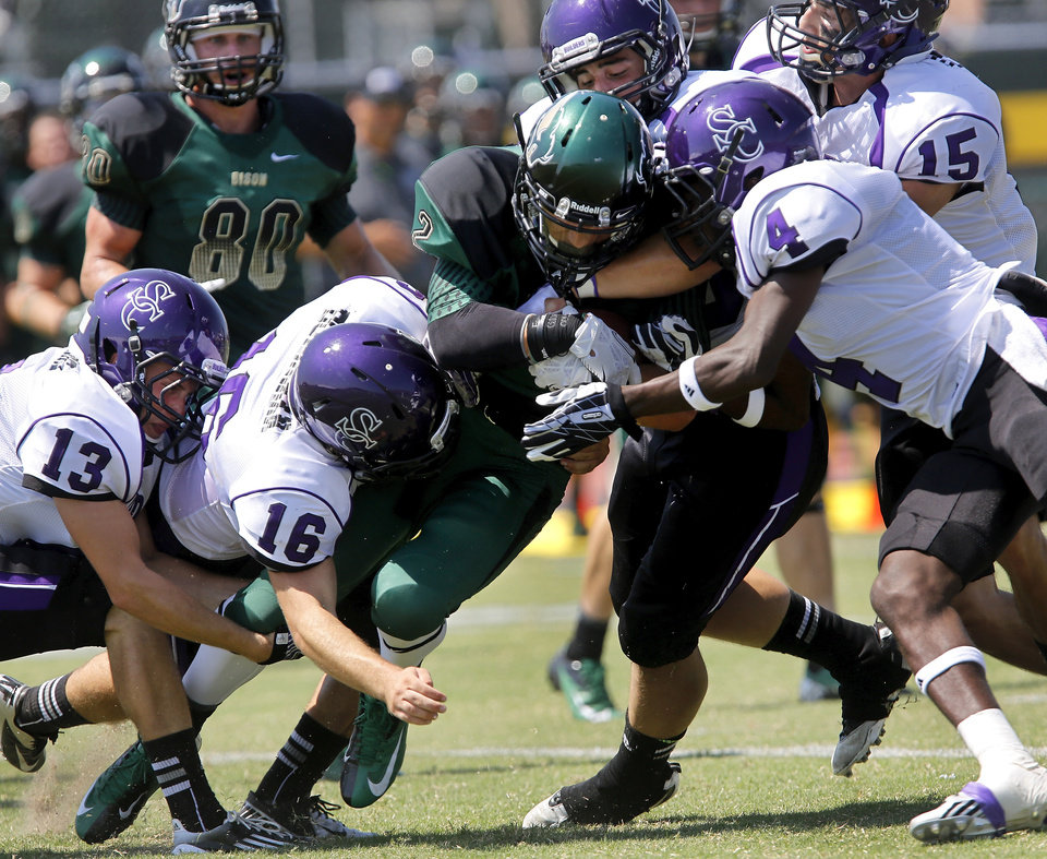 Photo - Bison player Nyko Symonds continues to drive after running into a wall of Southwestern College defenders. The Oklahoma Baptist University football team  took to the field on the school's Shawnee campus for the first time in more than seven decades when they hosted the Southwestern College(Kansas) Moundbuilders  at Bison Field in the Eddie Hurt Athletic Center on Saturday, Aug. 31, 2013. The Bison team was defeated today, 26-22. Prior to the 2013 season opener, the Bison football team played their last game in 1940. Photo  by Jim Beckel, The Oklahoman.         The Oklahoma Baptist University football team  took to the field on the school's Shawnee campus for the first time in more than seven decades when they hosted the Southwestern College(Kansas) Moundbuilders  at Bison Field in the Eddie Hurt Athletyic Center on Saturday, Aug. 31, 2013. The Bison team was defeated today, 26-22. Prior to the 2013 season opener, the Bison football team played their last game in 1940. Photo  by Jim Beckel, The Oklahoman.