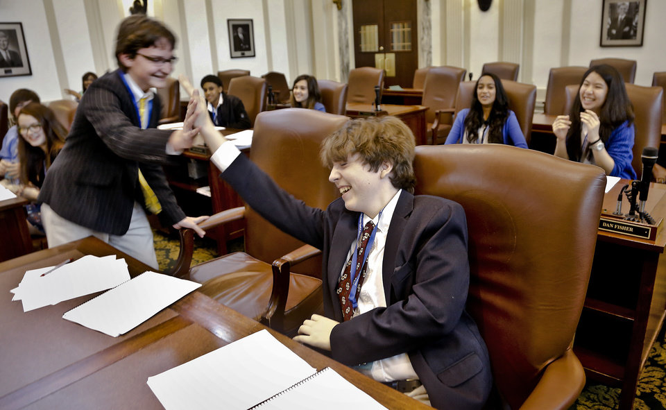 Edward Armitage, left, is given a high five from Lauren Grissom as about 100 seventh and eight grade students from across the state assume roles of state legislators at the State Capitol on Friday, March 29, 2013, in Oklahoma City, Okla.  Photo by Chris Landsberger, The Oklahoman