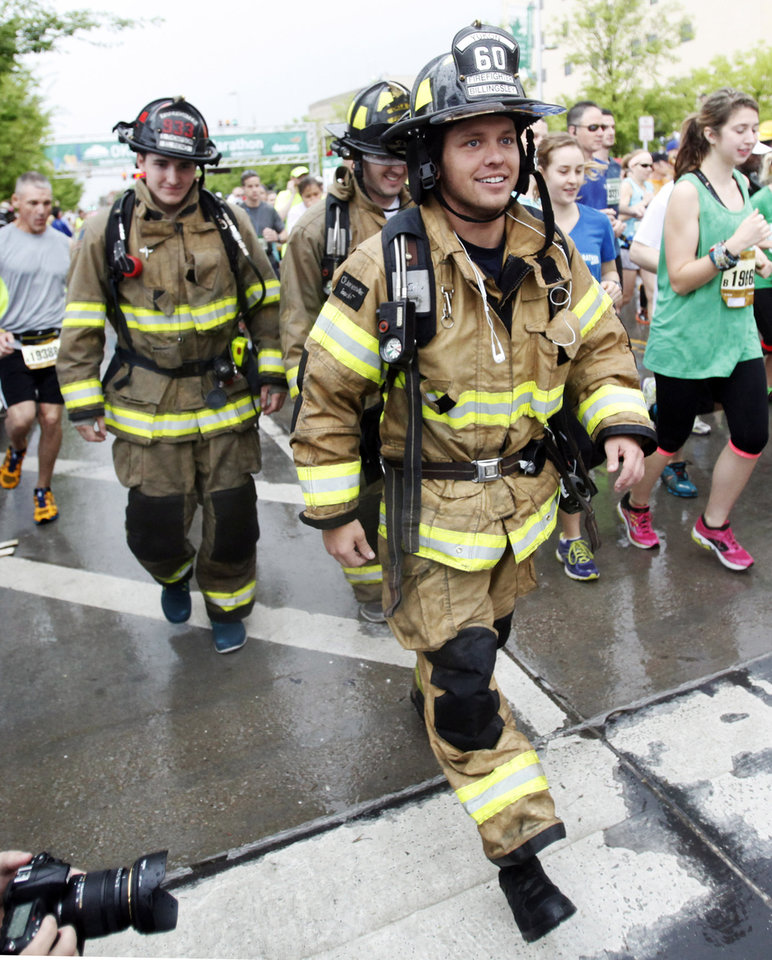 Photo - A group of three fireman walk away from the starting line of the 14th Annual Oklahoma City Memorial Marathon in Oklahoma City, Sunday, April 27, 2014. The marathon was delayed over two hours beyond it's original start time of 6 a.m. Photo by KT King/The Oklahoman