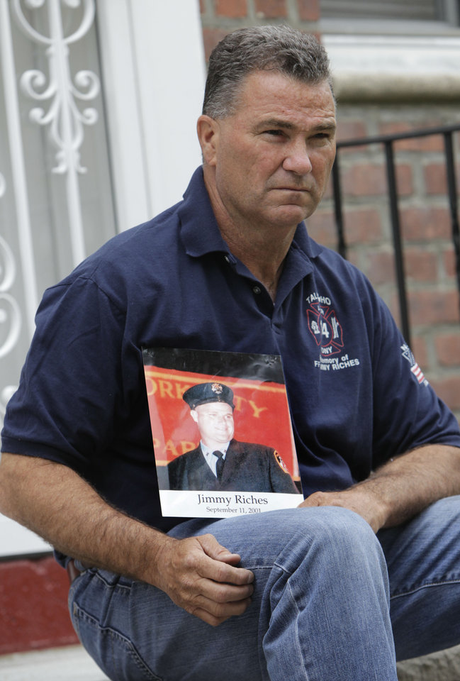 Photo -   Retired firefighter Jim Riches poses for a picture with a photography of his son near his home in New York, Thursday, May 3, 2012. Riches, whose son was killed during the 2001 terrorist attacks on the World Trade center, will be among those to watch the arraignment of Khalid Sheikh Mohammed. The arraignment of the self-proclaimed mastermind of the Sept. 11 terror attacks and four other Guantanamo Bay prisoners will be broadcast to only six sites at four military bases in the U.S. Northeast, a Pentagon spokesman said Monday. (AP Photo/Seth Wenig)