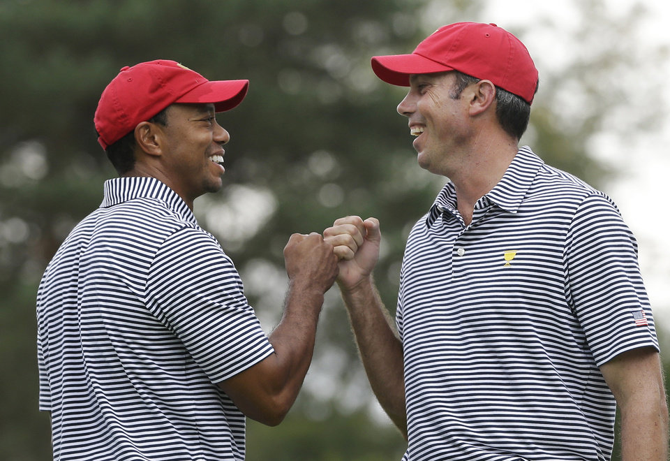 Photo - United States team player Tiger Woods, left, and team player Matt Kuchar fist bump after Kuchar made a birdie putt on the fourth hole during a foursome match at the Presidents Cup golf tournament at Muirfield Village Golf Club, Friday, Oct. 4, 2013, in Dublin, Ohio. (AP Photo/Darron Cummings)