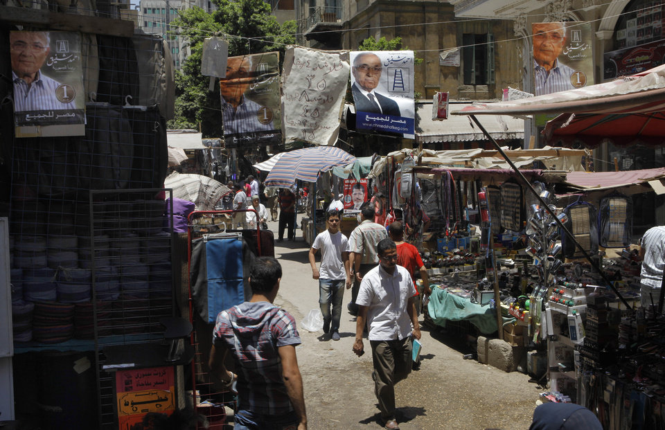 Photo -   Campaign posters supporting Egyptian presidential candidate Ahmed Shafiq, the last prime minister of deposed president Hosni Mubarak, hang above a popular market in Cairo, Egypt, Tuesday, June 12, 2012. Arabic on the banners reads: