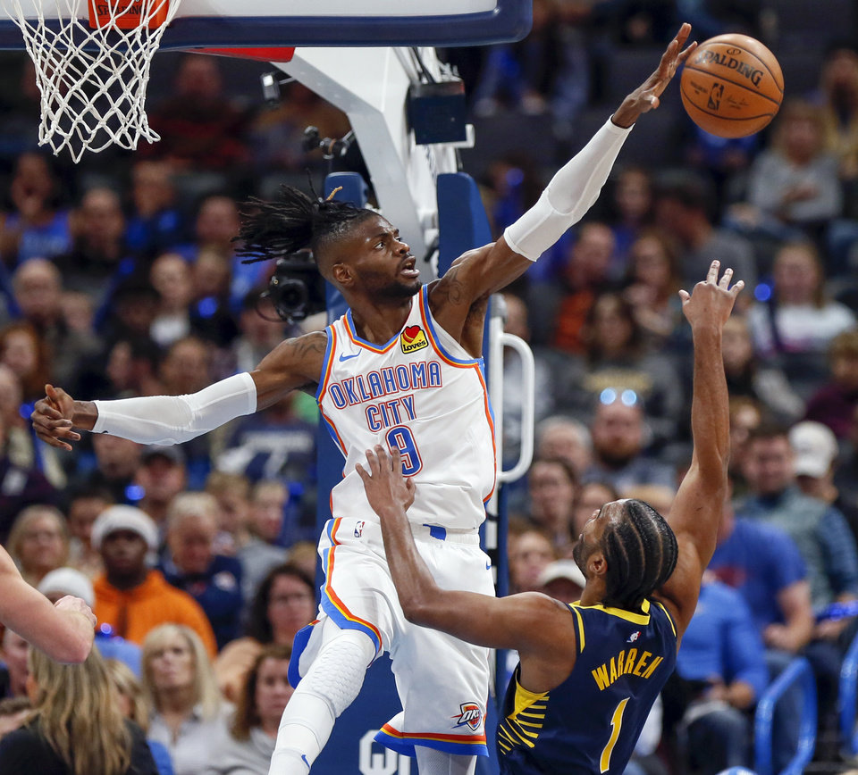 Photo - Oklahoma City's Nerlens Noel (9) blocks a shot by Indiana's T.J. Warren (1) in the second quarter during an NBA basketball game between the Indiana Pacers and the Oklahoma City Thunder at Chesapeake Energy Arena in Oklahoma City, Wednesday, Dec. 4, 2019. [Nate Billings/The Oklahoman]