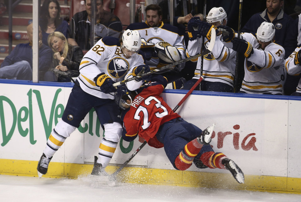 Photo - Florida Panthers' Brandon Pirri (73) slams into the wall as he and Buffalo Sabres' Marcus Foligno (82) fight for the puck during the first period of an NHL hockey game in Sunrise, Fla., Friday, March 7, 2014. (AP Photo/J Pat Carter)