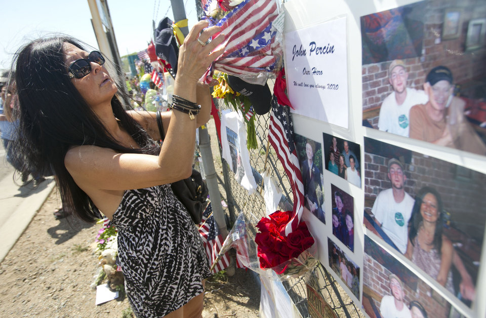 Photo - Jeanette Moore of Phoenix, the aunt of fallen firefighter John Percin puts up a remembrance in photos to her nephew adding to the memorial for the fallen firefighters in front of Prescott Fire Station #7 on Tuesday, July 2, 2013.  Eighteen firefighters from Prescott Fire Department's Granite Mountain Hotshots  team and a 19th firefighter from another crew were killed battling the Yarnell Hill Fire on Sunday. The Granite Mountain Hotshots were based out of Prescott Fire Station #7.   (AP Photo/The Arizona Republic, David Wallace)