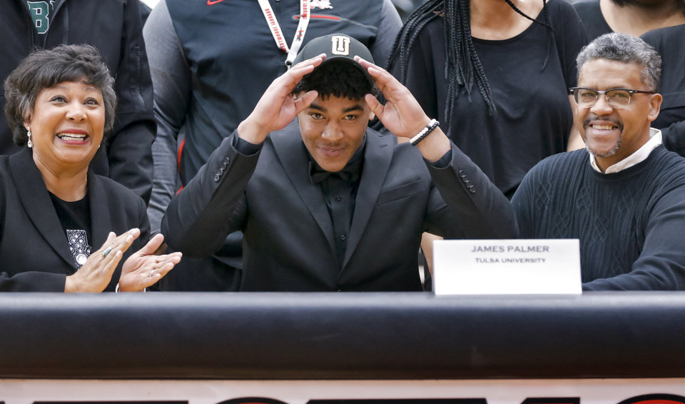 Photo - Westmoore's James Palmer puts on his hat after signing his letter of intent  to play football for Tulsa University during national signing day at Westmoore High School in Moore, Okla. on Wednesday, Feb. 7, 2018.  Photo by Chris Landsberger, The Oklahoman