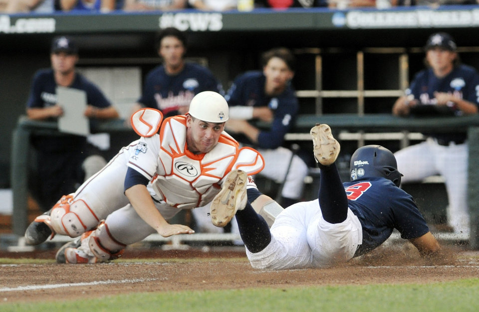 Photo - Vanderbilt's Zander Wiel, right, slides safely into home plate for a run against Virginia catcher Nate Irving in the third inning of game one of the best-of-three NCAA baseball College World Series finals in Omaha, Neb., Monday, June 23, 2014.  (AP Photo/Eric Francis)