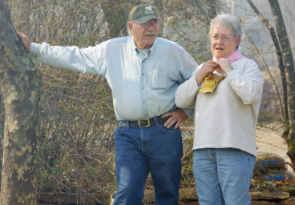 Photo - Frank and Susan Holley watch as firemen douse flames less than 100 feet from their home as a large grass fire burns on Friday, March 11, 2011, in Goldsby, Okla. Photo by Steve Sisney, The Oklahoman