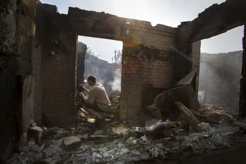 Photo - A journalist films a destroyed house following a mortar attack in Semyonovka village, outside Slovyansk, Ukraine, Friday, May 23, 2014. The village on the outskirts of Slovyansk, a city which has been the epicenter of clashes for weeks, has seen continuous shelling by the Ukrainian government forces, who have retaliated to the rebel fire. On Friday, the private house was destroyed by mortar fire that came from the Ukrainian side. There were no casualties, as the family living there had left the previous day, according to local residents. (AP Photo/Alexander Zemlianichenko)