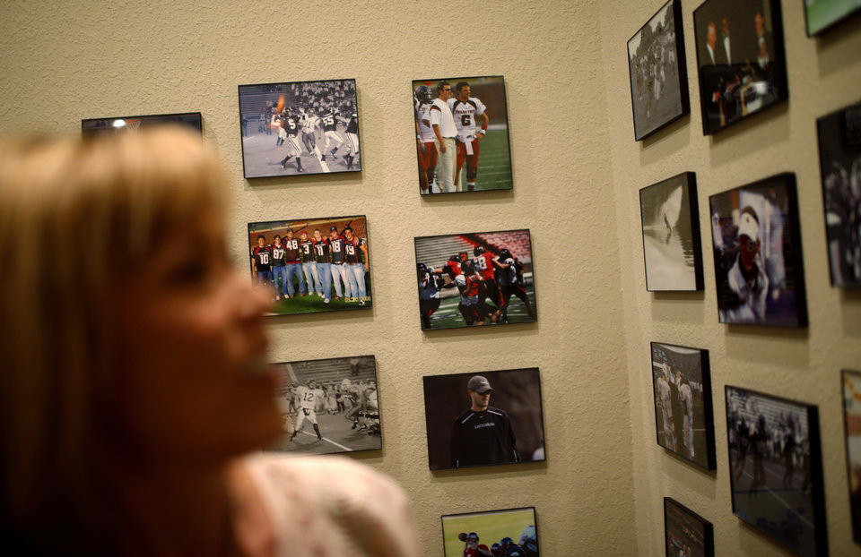Photo - Marilyn Riley looks over photos of her son  Lincoln Riley, Oklahoma's offensive coordinator, and his brother Garrett Riley inside her home in Muleshoe, Texas, on Thursday, June 25, 2015. Photo by Bryan Terry, The Oklahoman