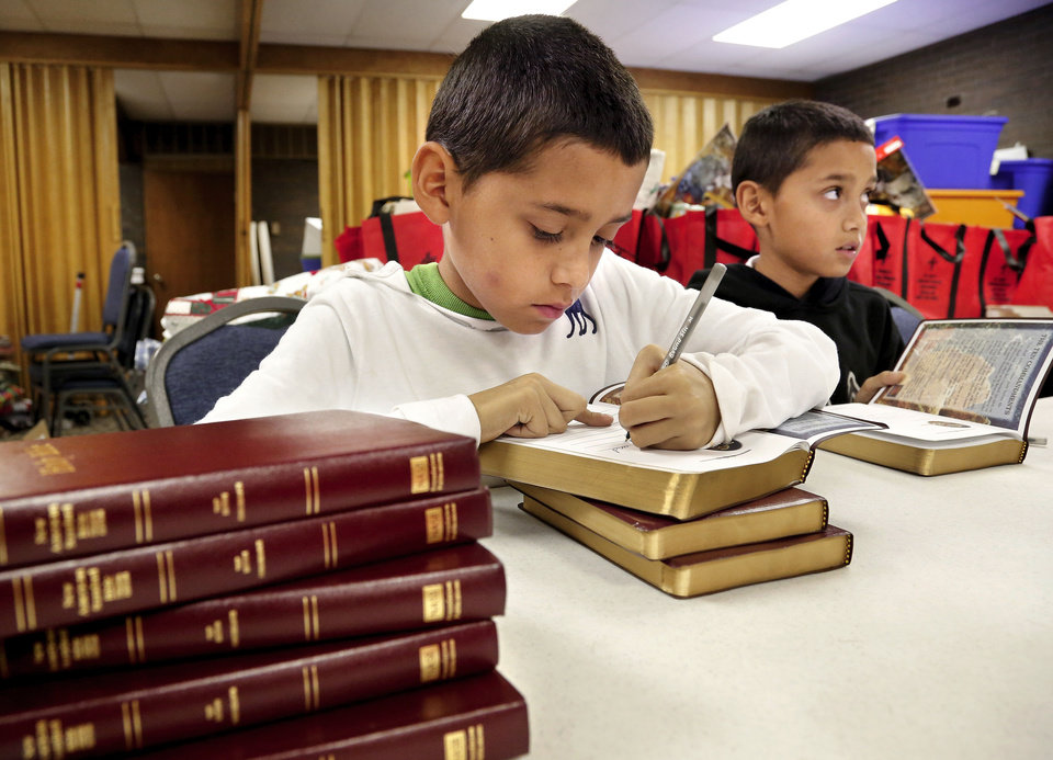 Photo - Aaron Ruiz and other children from St. John's Lutheran School write personal notes on the front pages of Bible that will be given away as part of the CHRISTMAS Cares Moore outreach event at St. John's Lutheran Church in Moore.   Jim Beckel - THE OKLAHOMAN