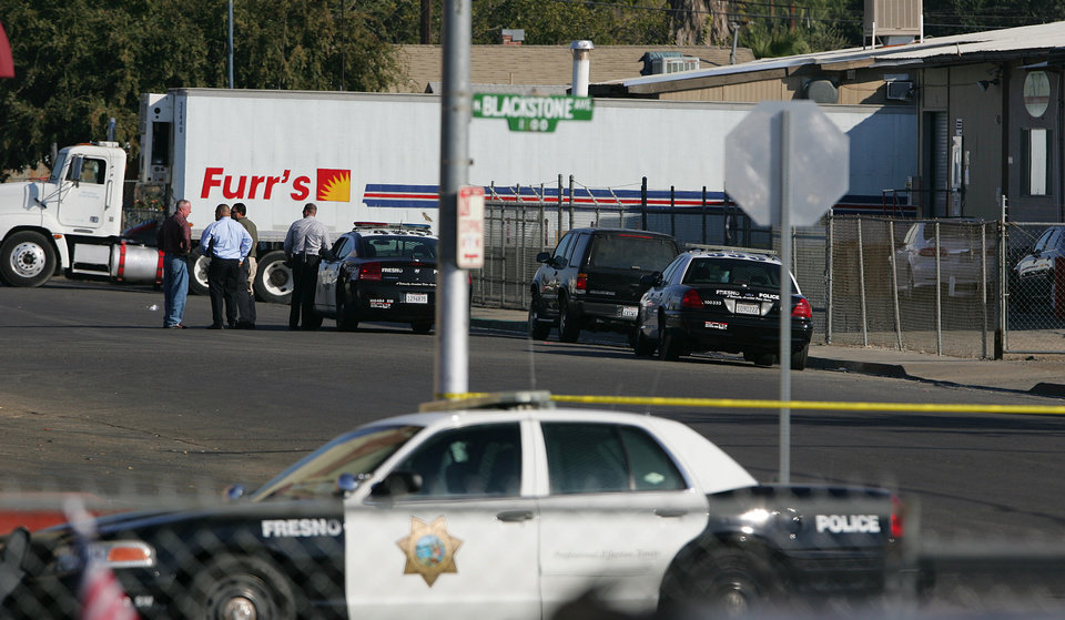 Fresno police officers look over the area where a man killed himself after shooting people in his workplace that killed at least one person and wounded several others at Valley Protein, formally known as Apple Valley Farms Tuesday, Nov. 6, 2012, in Fresno, Calif. Police say a parolee who worked at the Fresno chicken processing plant opened fire at the business on Tuesday, killing one person and wounding three others, before shooting himself. Police Chief Jerry Dyer said they didn't know what prompted the attack by 42-year-old Lawrence Jones midway through his shift at Apple Valley Farms. Other workers told police he did not appear to be himself when he arrived at the plant for work.(AP Photo/Gary Kazanjian)