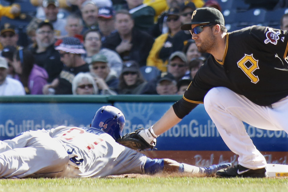 Photo - Pittsburgh Pirates first baseman Travis Ishikawa, right, reaches to tag Chicago Cubs Emilio Bonifacio as he dives back to first on a pickoff attempt in the tenth inning the opening day baseball game on Monday, March 31, 2014, in Pittsburgh. The Pirates won 1-0 in ten innings. Bonifacio was initially called safe by the first base umpire, but the call was overturned on a review requested by manager Clint Hurdle and Bonifacio was ruled out. (AP Photo/Keith Srakocic)