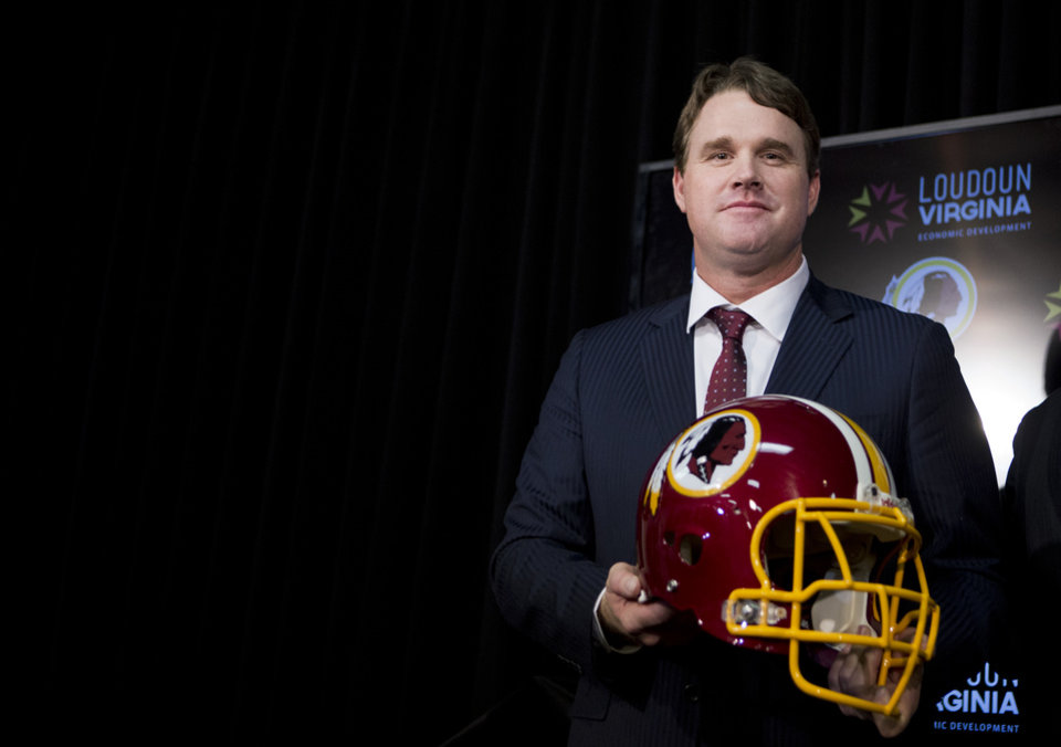 Photo - New Washington Redskins head coach Jay Gruden holds a Redskins helmet at the Redskins Park in Ashburn, Va., Thursday, Jan. 9, 2014.  Jay Gruden was introduced as the new Washington Redskins head coach, replacing Mike Shanahan and becoming the team's eighth head coach since Daniel Snyder purchased the franchise in 1999. (AP Photo/Manuel Balce Ceneta)