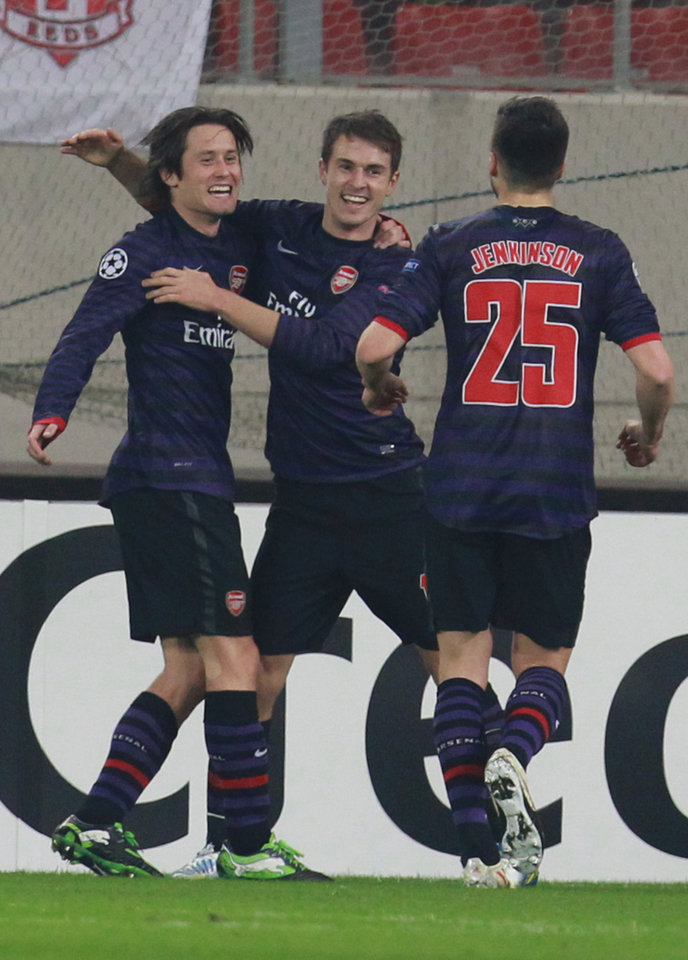 Photo - Arsenal's Tomas Rosicky, left, celebrates scoring against Olympiakos with Aaron Ramsey and Carl Jenkinson, right, during a group B Champions League soccer match in the port of Piraeus, near Athens, Tuesday, Dec. 4, 2012. (AP Photo/Thanassis Stavrakis)