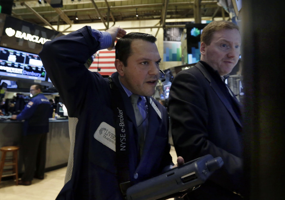 Photo - Trader Michael Zicchinolfi, left, works on the floor of the New York Stock Exchange, Monday, March 3, 2014. Global stock markets are down sharply on tensions over Russia's military advance into Ukraine and the threat of sanctions by Western governments. (AP Photo/Richard Drew)