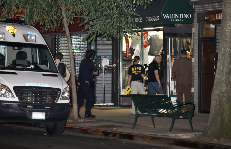 In this early Saturday, July 7, 2012 photo, authorities investigate the crime scene where clothing store owner Mohamed Gebeli was killed inside Valentino Fashion in the Bay Ridge neighborhood in the Brooklyn borough of New York. The same gun that killed Gebeli was also used in the murders of two other shopkeepers, according to police, with the latest victim being fatally shot Friday, Nov. 16, 2012, in Brooklyn's Flatbush neighborhood. (AP Photo/David Boe)