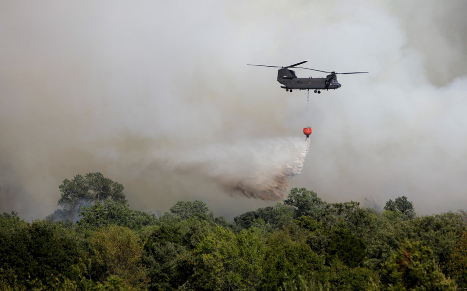 Photo - A helicopter dumps water on a wildfire near NW 122nd and Midwest Blvd. in Oklahoma City, Wednesday, August 31, 2011. Photo by Bryan Terry, The Oklahoman
