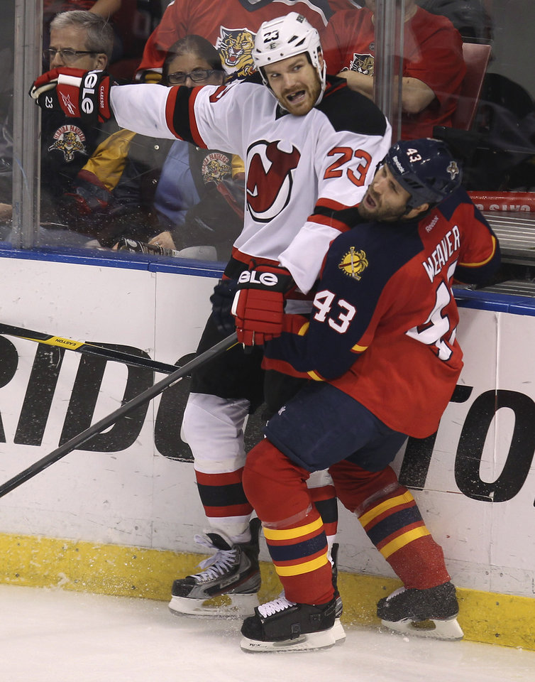 Photo -   New Jersey Devils' David Clarkson (23) and Florida Panthers Mike Weaver (43) slam into each other during the third period of Game 7 in a first-round NHL Stanley Cup playoff hockey series, in Sunrise, Fla., Wednesday, April 26, 2012. (AP Photo/J Pat Carter)