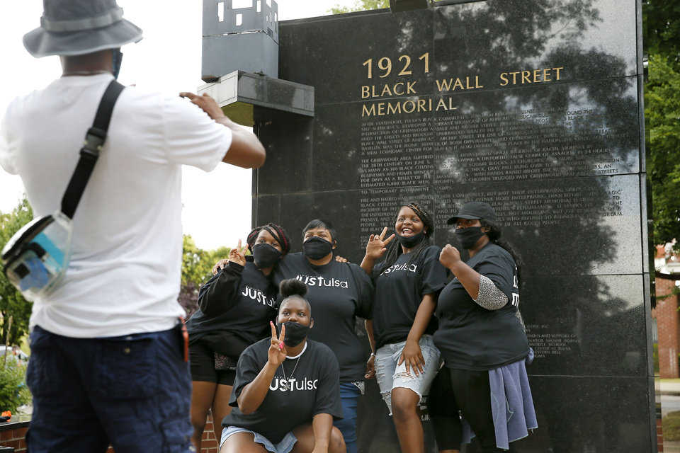Photo - A family from Kansas City poses for a photo in front of the 1921 Black Wall Street Memorial in the Greenwood District during a Juneteenth celebration in Tulsa, Okla., Friday, June 19, 2020.  [Bryan Terry/The Oklahoman]