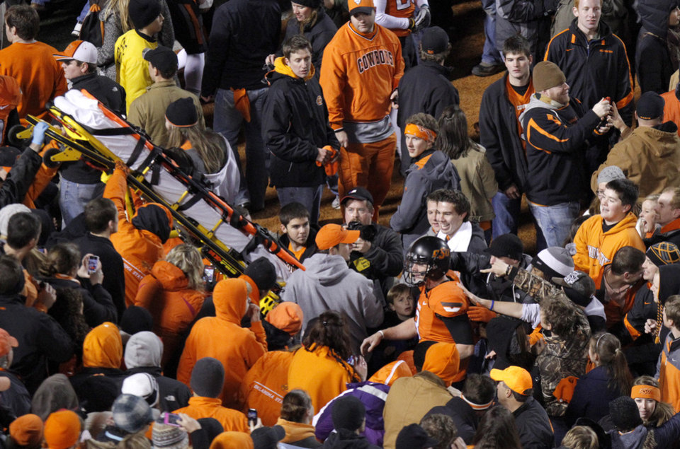 Photo - A stretcher is passed down to the field as Oklahoma State's Brandon Weeden (3) makes his way out of the crowd following the Bedlam college football game between the Oklahoma State University Cowboys (OSU) and the University of Oklahoma Sooners (OU) at Boone Pickens Stadium in Stillwater, Okla., Saturday, Dec. 3, 2011. Photo by Bryan Terry, The Oklahoman