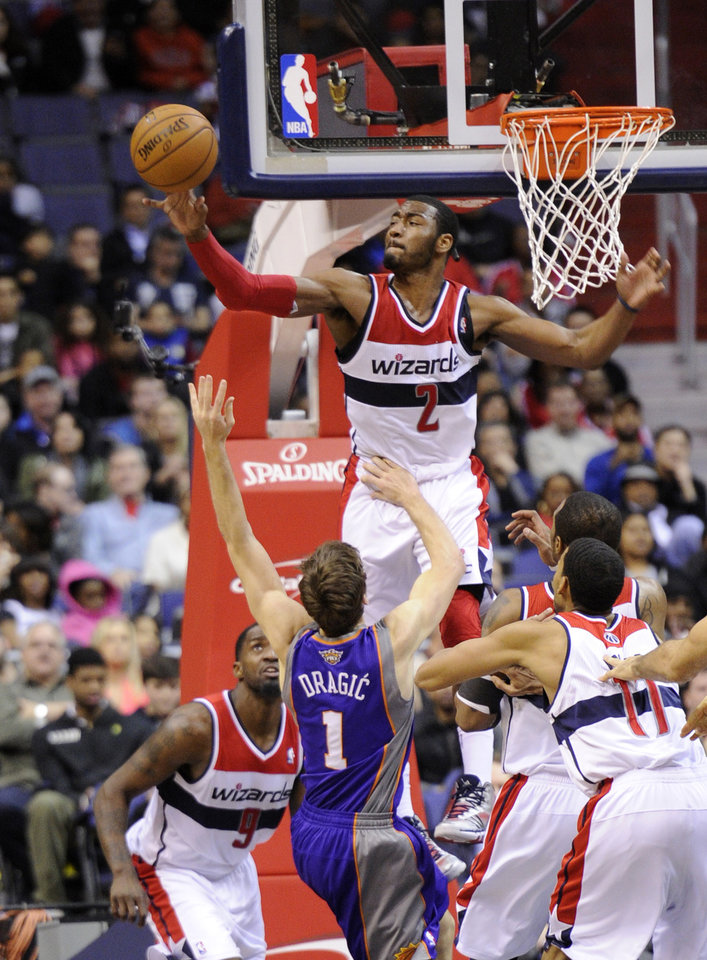 Photo - Washington Wizards point guard John Wall (2) defends the basket against Phoenix Suns point guard Goran Dragic (1), of Slovenia, during the second half of an NBA basketball game on Saturday, March 16, 2013, in Washington. Wizards forward Martell Webster (9) watches the action. The Wizards won 127-105. (AP Photo/Nick Wass)