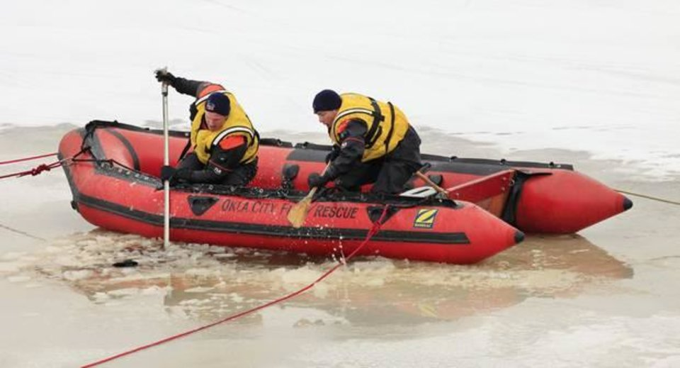 Photo - Oklahoma City fire department divers check a pond behind businesses in the 12300 block of Market Drive near NW 122 Street and Kelley Ave. Street in Oklahoma City Friday, Feb. 7, 2014. Footprints were seen going to and from a hole in the ice on the pond and a glove and beanie found near the hole. The pond is seven feet deep where the hole was. Photo by Paul B. Southerland, The Oklahoman