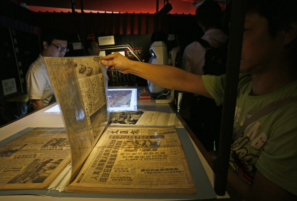 Photo - In this May 28, 2014 photo, a visitor reads old newspapers reporting the June 4, 1989 crackdown on pro-democracy protesters, at the June 4th Museum in Hong Kong. The 75 square meters (800 square feet) June 4th Museum is the world's only museum chronicling the brutal crackdown on the 1989 Tiananmen protests. (AP Photo/Vincent Yu)