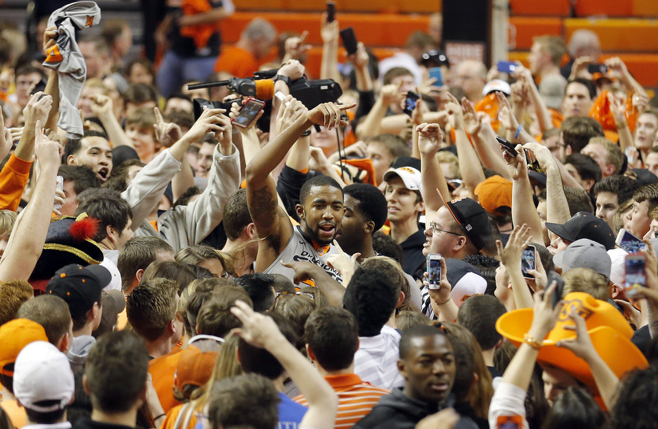 Photo - Oklahoma State's Michael Cobbins (20) celebrates with fans following the men's college basketball game between Oklahoma State University and the University of Kansas at Gallagher-Iba Arena in Stillwater, Okla.,  Saturday, Feb. 7, 2015. OSU won 67-62. Photo by Sarah Phipps, The Oklahoman