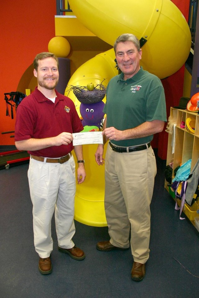 Uwe von Schamann (right), director of development for the J. D. McCarty Center, accepts a check for $333 from James Robb, community director for the St. Thomas Moore Knights of Columbus Council 8523 in Norman. This is the 10th year that Council 8523 has donated some of the proceeds from their annual Tootsie Roll candy drive in support of the McCarty Center.<br/><b>Community Photo By:</b> Greg Gaston<br/><b>Submitted By:</b> Greg, Norman