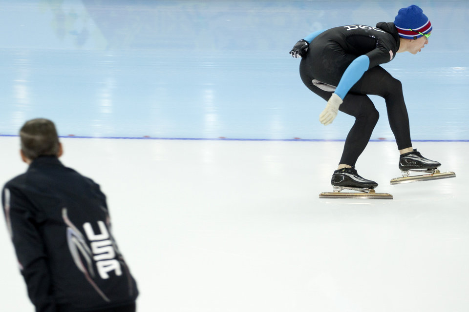 Photo - One of the coaches of the U.S. Speedskating team watches athlete Jonathan Kuck warm-up wearing the old World Cup race suit, prior to the men's 1,500-meter race at the Adler Arena Skating Center during the 2014 Winter Olympics in Sochi, Russia, Saturday, Feb. 15, 2014. U.S. skaters are looking to bounce back from an awful start to their Olympics by slipping back into their old suits that should have been made obsolete by new high-tech gear. (AP Photo/Peter Dejong)
