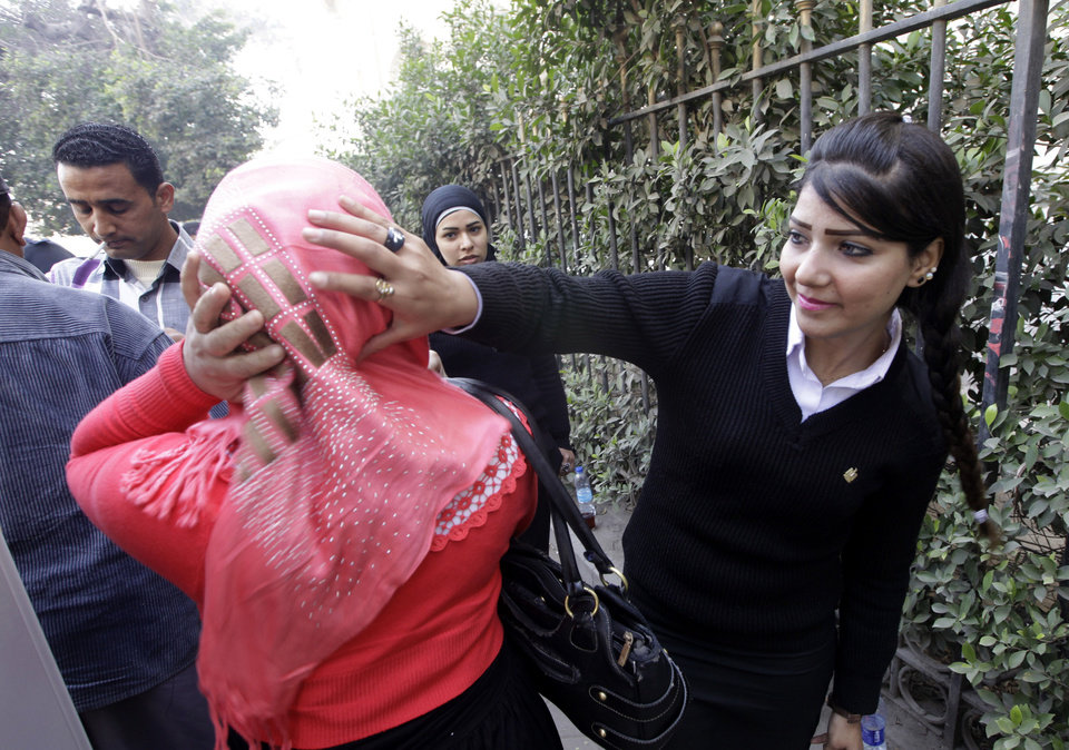 Photo - An Egyptian policewoman checks the veil of a visitor at the entrance of Tahrir Square, the epicenter of the 2011 uprising, in Cairo, Egypt, Saturday, Jan. 25, 2014. An Egyptian masked policeman guards Cairo's state security chief, Osama al-Saghir, third right, as he visits Tahrir Square, the epicenter of the 2011 uprising, in Cairo, Egypt, Saturday, Jan. 25, 2014.(AP Photo/Amr Nabil)