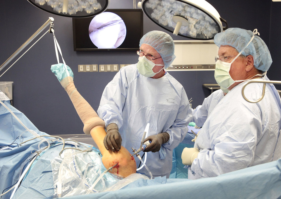 Photo - Dr. David Holden performs arthroscopic rotator cuff surgery at McBride Orthopedic Hospital in Oklahoma City. The patient's arm is tied up in the lateral decubitus position, a common position for this type of surgery.  David McDaniel - The Oklahoman
