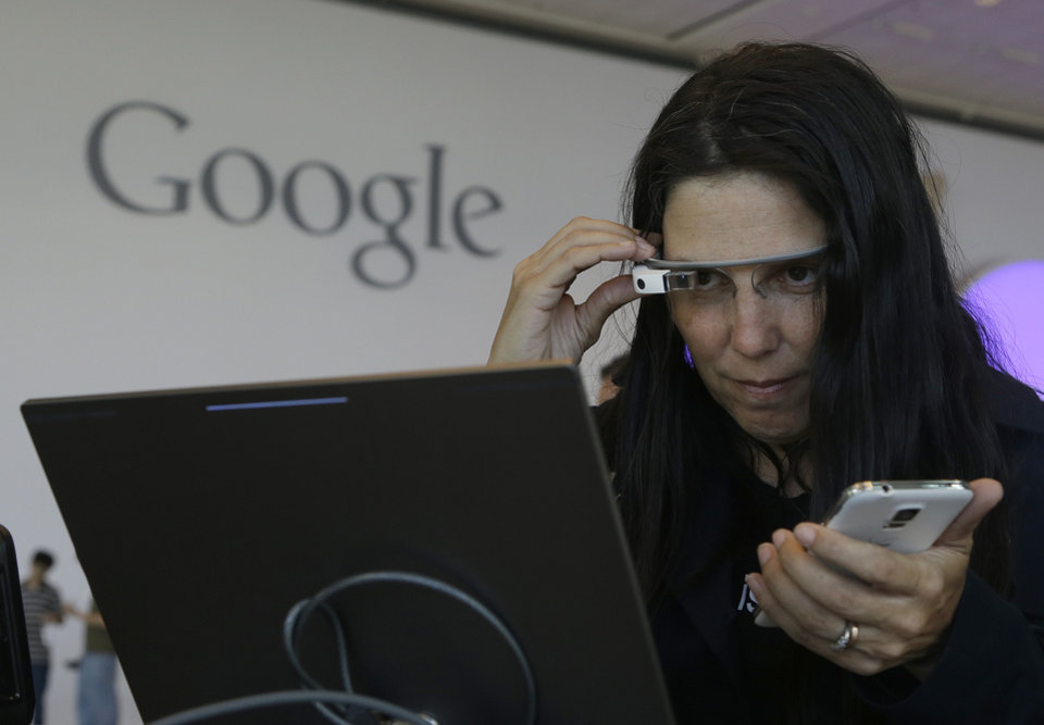 Photo - Cecilia Abadie, founder of 33 Labs, uses a pair of Google Glass as she registers for Google I/O 2014 at the Moscone Center in San Francisco, Tuesday, June 24, 2014. (AP Photo/Jeff Chiu)