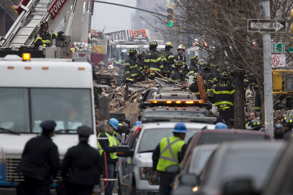 Photo - Firefighters respond to an explosion that leveled two apartment buildings in the East Harlem neighborhood of New York, Wednesday, March 12, 2014. Con Edison spokesman Bob McGee says a resident from a building adjacent to the two that collapsed reported that he smelled gas inside his apartment, but thought the odor could be coming from outside. (AP Photo/John Minchillo)