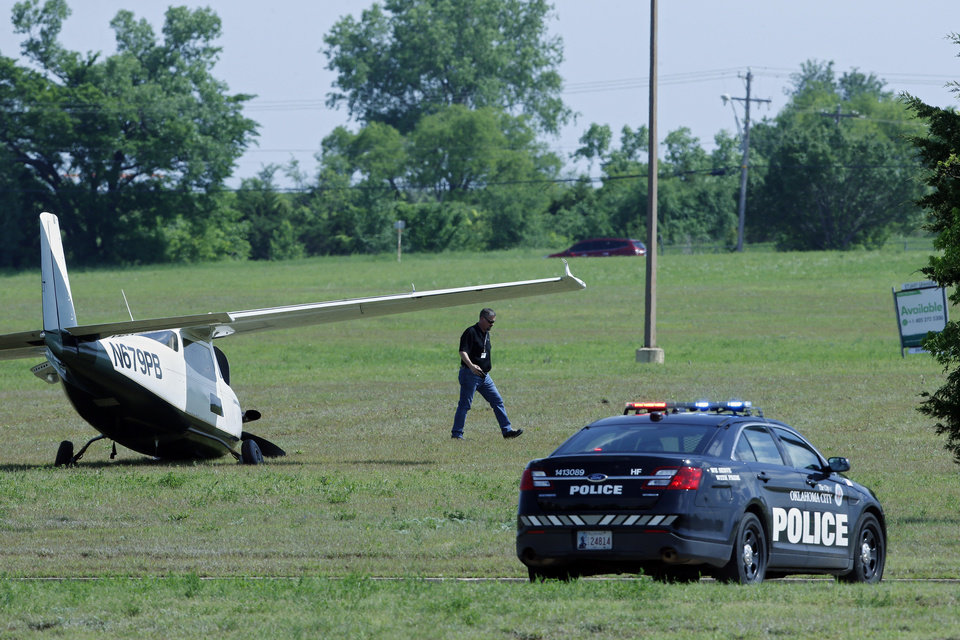 Photo - An official walks around a small plane which made an emergency landing in a field Monday, May 6, 2019, in Oklahoma City. Oklahoma City firefighters say the pilot of the small plane made an emergency landing along a roadway when the aircraft had mechanical problems heading to an airport. (AP Photo/Sue Ogrocki)