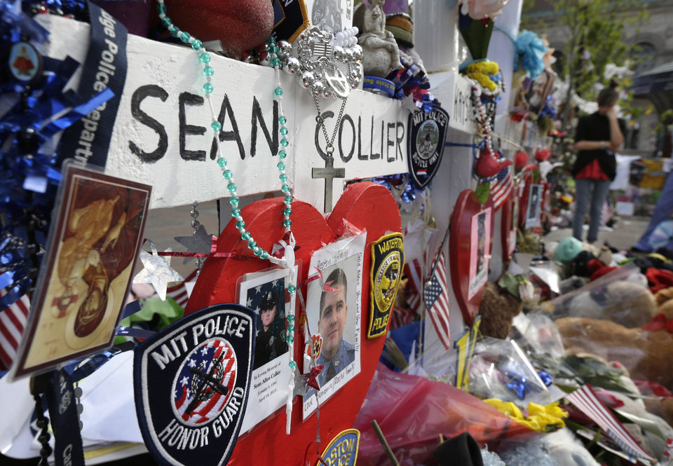 Photo - Photographs of slain Massachusetts Institute of Technology campus officer Sean Collier, center, are part of a makeshift memorial near the Boston Marathon finish line in Boston's Copley Square Tuesday, May 7, 2013 in remembrance of the Boston Marathon bombings. Authorities allege that the Boston Marathon bombing suspects were responsible for Colliers death. (AP Photo/Steven Senne)