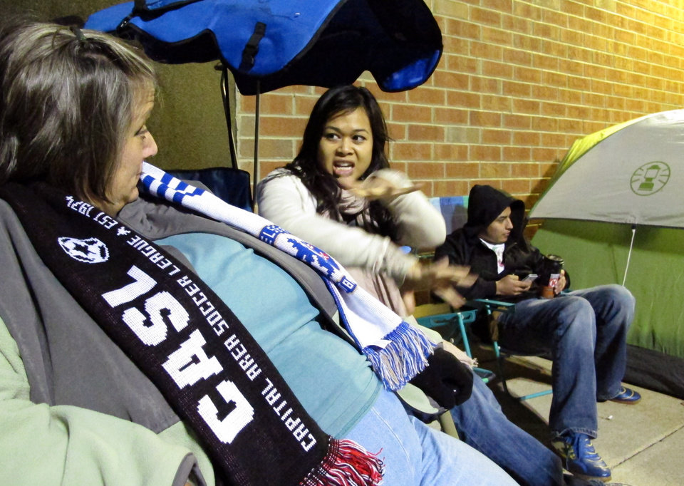 Karen Jefferson, left, chats with Michelle Phan as they wait outside a Best Buy store in Raleigh, N.C., on Thursday, Nov. 22, 2012. The two had been camped out since Wednesday evening, missing Thanksgiving dinners with family in hopes of getting great deals on flat-screen televisions. (AP Photo/Allen Breed)