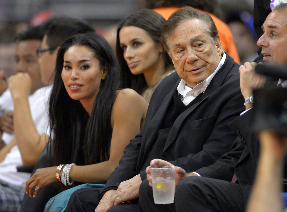 Photo - FILE - In this file photo taken on Friday, Oct. 25, 2013, Los Angeles Clippers owner Donald Sterling, right, and V. Stiviano, left, watch the Clippers play the Sacramento Kings during the first half of an NBA basketball game in Los Angeles. Used car dealership chain CarMax says it is ending its sponsorship of the Clippers in the wake of racist comments attributed to Sterling. (AP Photo/Mark J. Terrill, File)