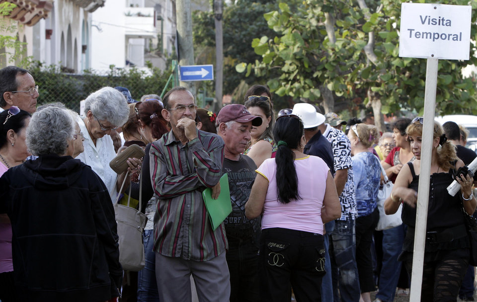 Photo - In this Jan. 7, 2013 photo, people wait to enter the U.S. Interests Section to apply for U.S. visas in Havana, Cuba. People are awaiting a new law taking effect Monday, Jan. 14, 2013 that will let the vast majority of Cubans travel abroad without having to ask for permission first or pay for costly exit visas. (AP Photo/Franklin Reyes)