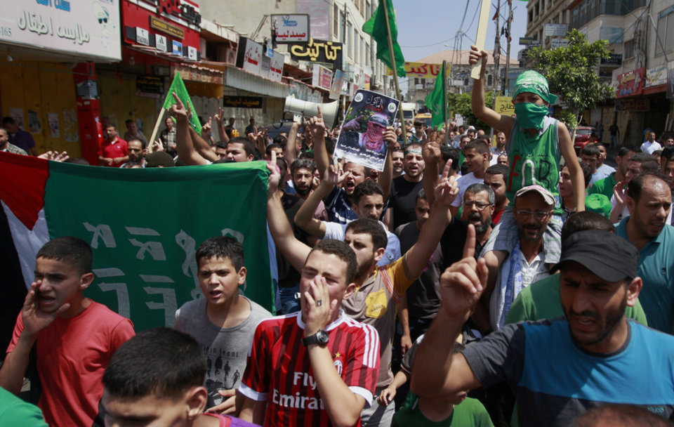 Photo - Palestinian supporters of Hamas chant slogans against the Israeli military action in Gaza, during a demonstration in the West Bank city of Jenin on Friday, Aug. 22, 2014. (AP Photo/Mohammed Ballas)