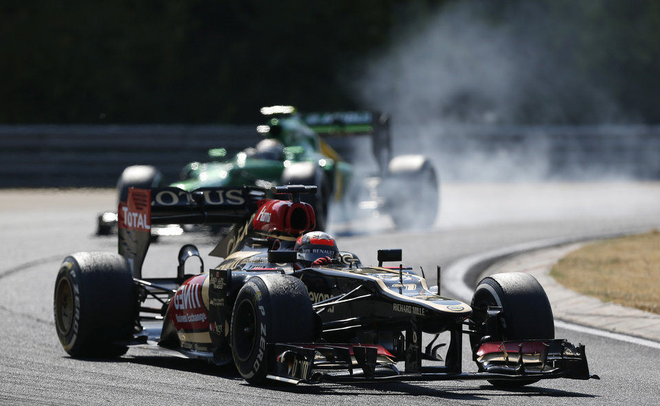 Photo - Lotus driver Romain Grosjean, down, of France steers his car ahead of Caterham driver Giedo Van Der Garde, top, of the Netherlands during the Hungarian Formula One race at the Hungaroring racetrack near Budapest, Hungary, Sunday, July 28, 2013. (AP Photo/Petr David Josek)