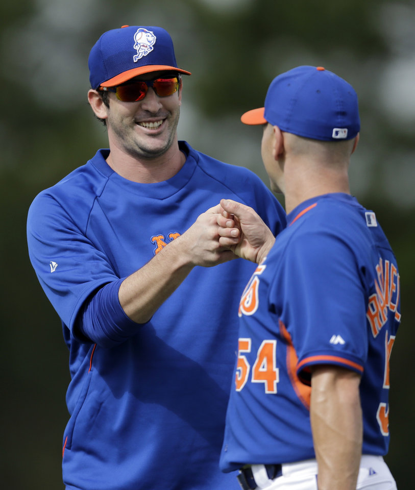 Photo - New York Mets pitcher Matt Harvey gets a fist bump from bullpen catcher Dave Racaniello after the two played catch during spring training baseball practice Saturday, Feb. 22, 2014, in Port St. Lucie, Fla. Harvey underwent Tommy John surgery on Oct. 22. (AP Photo/Jeff Roberson)