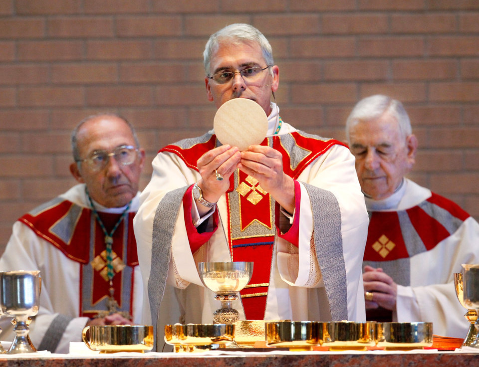 Photo -  The Most Rev. Paul S. Coakley, archbishop of the Archdiocese of Oklahoma City, holds a consecrated Eucharistic host in this photo taken at Coakley's 2011 installation Mass at St. John the Baptist Catholic Church in Edmond. The Eucharistic Host typically is a small wafer of unleavened bread considered by Catholics to be the body of Jesus Christ. Photo by Jim Beckel, The Oklahoman Archive   JIM BECKEL -