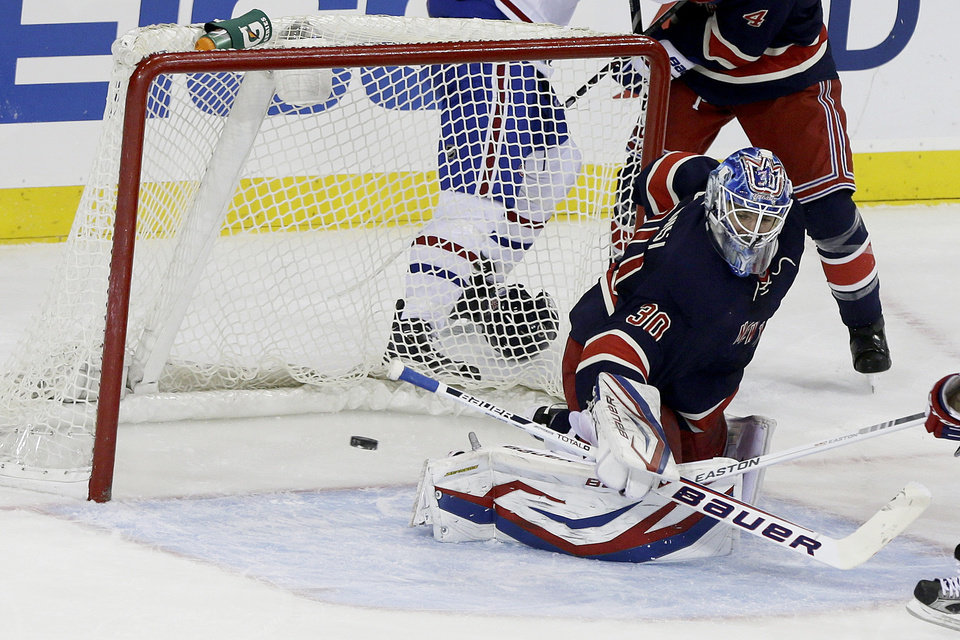 Photo - New York Rangers goalie Henrik Lundqvist, of Sweden, deflects a shot on the goal during the first period of an NHL hockey game against the Montreal Canadiens, Tuesday, Feb. 19, 2013, in New York. (AP Photo/Frank Franklin II)