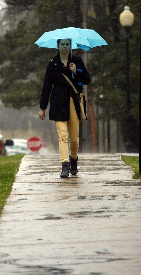 Photo - Belhaven University senior Lesliu Van Winkle of Grand Rapids, Mich., seeks the protection from the rain under her neon blue umbrella as she walks to class in Jackson, Miss., during a constant rain, Thursday, Jan. 10, 2013. These same rains also brought about isolated mudslides in Natchez, street flooding in Jackson and downed trees throughout the state. (AP Photo/Rogelio V. Solis)