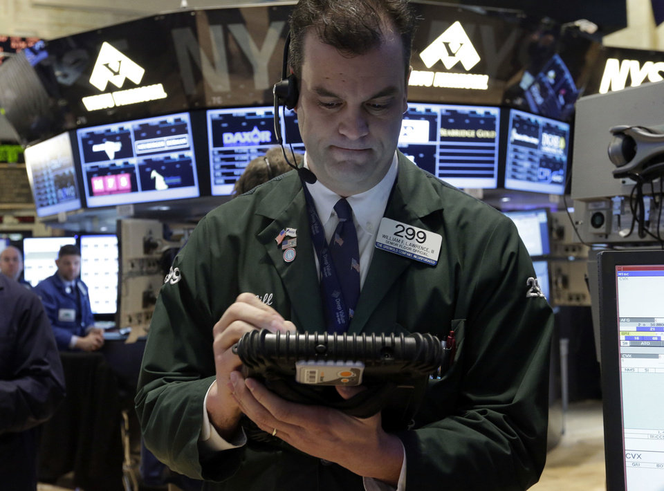 Trader William Lawrence works Friday on the floor of the New York Stock Exchange. AP Photo