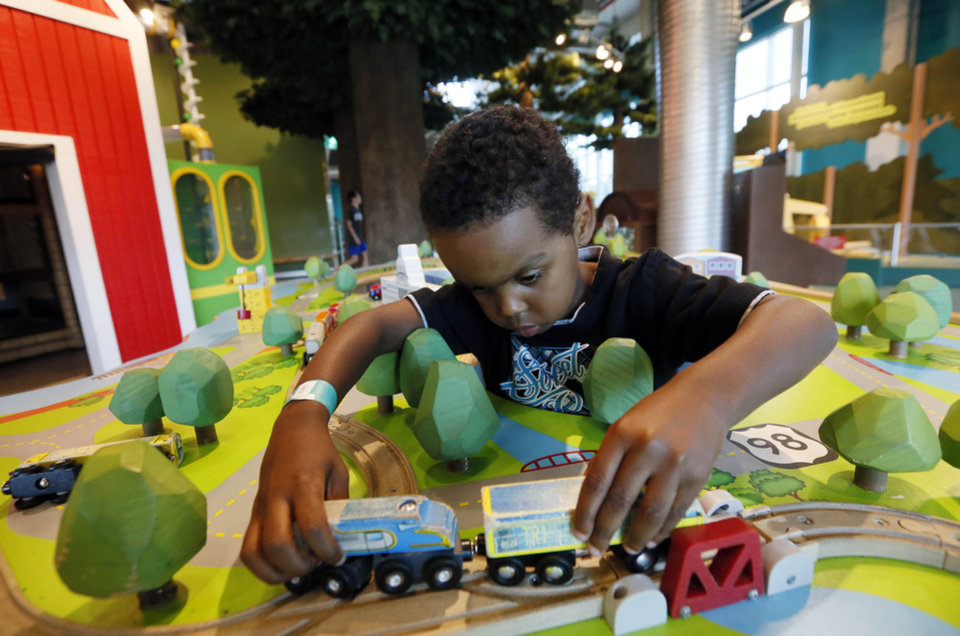 Photo - In this July 3, 2014 photograph, Julius Sessoms, 5, of Jacksonville, N.C., adjusts the truck and trailer at the Mississippi Children's Museum in Jackson, Miss. The interactive hands-on facility promotes literacy, health and nutrition, learning the state's heritage and exploration of its cultural arts and key economic industries in a fun setting. (AP Photo/Rogelio V. Solis)