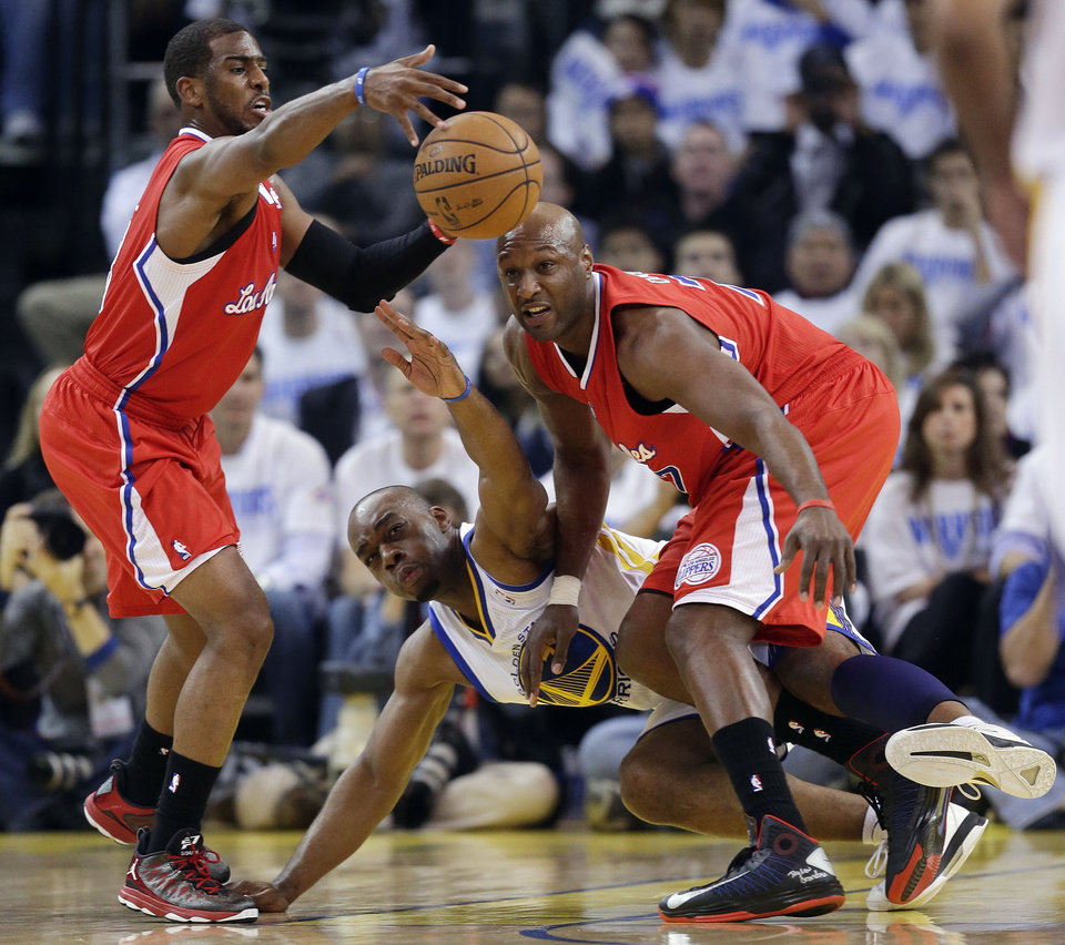 Los Angeles Clippers' Chris Paul, left, grabs a loose ball next to Golden State Warriors' Carl Landry, bottom center, and teammate Lamar Odom, right, during the first half of an NBA basketball game in Oakland, Calif., Wednesday, Jan. 2, 2013. (AP Photo/Marcio Jose Sanchez)